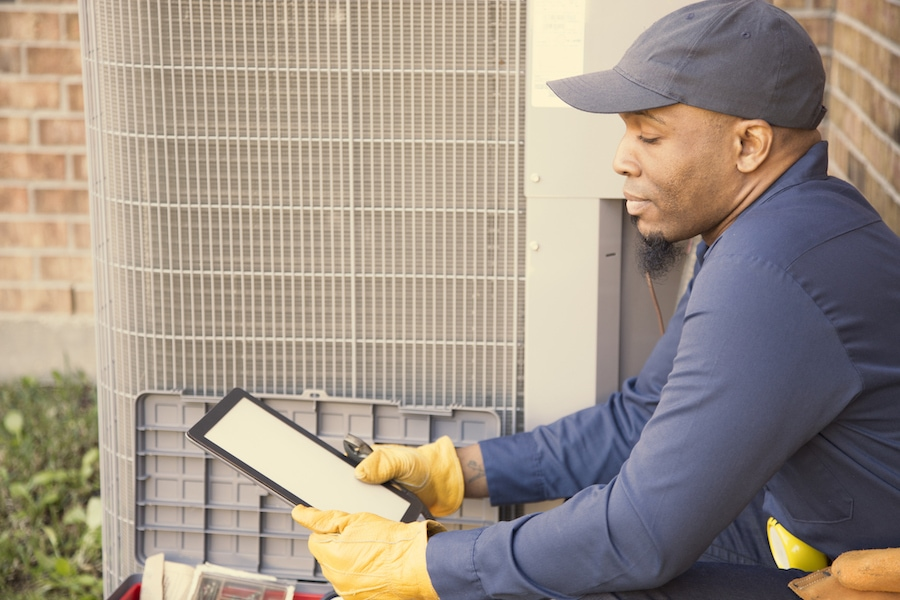 African descent, blue collar air conditioner repairman at work. He refers to digital tablet for next steps.